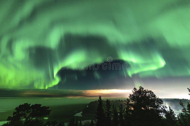 Visa lysande grönt Aurora som lyser över svensk skogslandskap i berg, ljusstrålar från en by och norra fotografering för bildbyråer
