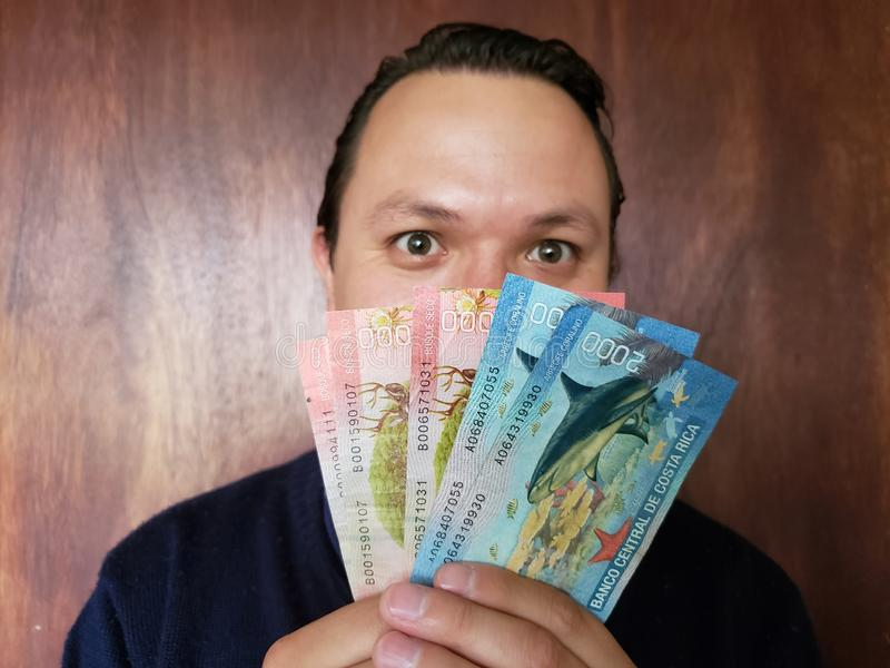 visage avec l'expression d'émotion d'un jeune homme et de tenir des billets de banque de Costa Rican images libres de droits