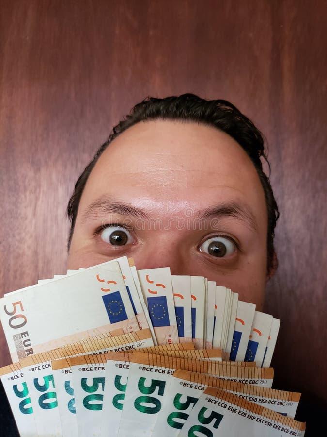 visage avec l'expression d'émotion d'un jeune homme et des billets de banque européens image libre de droits