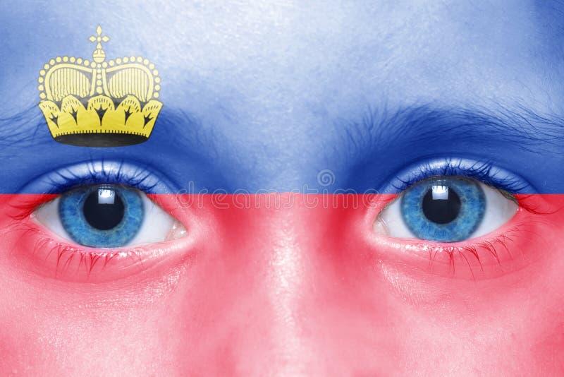 visage avec le drapeau de la Liechtenstein photographie stock libre de droits