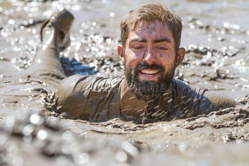Visage barbu de sourire couvert dans la boue image stock
