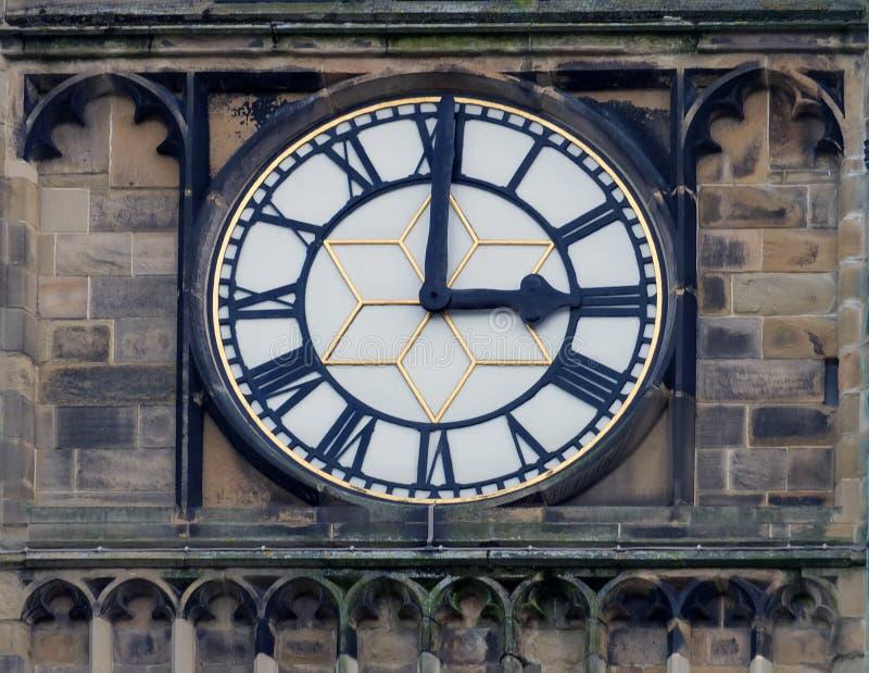 Visage blanc d'horloge d'église avec les chiffres romains à l'horloge de trois o images stock