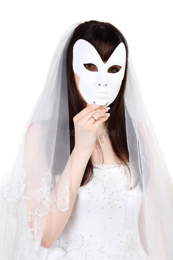 Visage caché belle par mariée derrière le masque photos stock