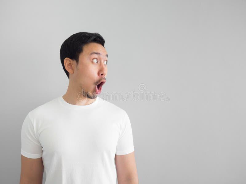 Visage choqué de l'homme dans la chemise blanche sur le fond gris photo libre de droits