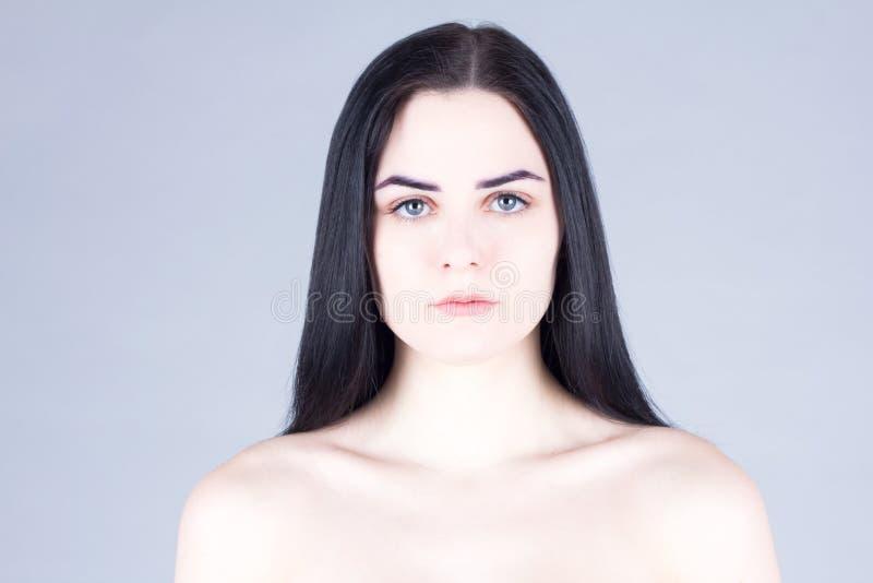 Visage clair d'une femme avec les cheveux foncés, les yeux gris et la peau juste photos stock