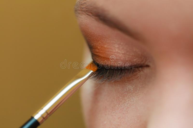 Close up woman getting make up, eyeshadow stock photos