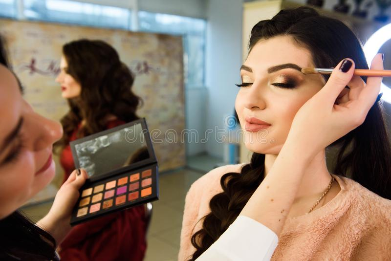 Visage concept. Close up woman getting make up on eyelids. Applying eyeshadow with brush by professional artist. stock photo