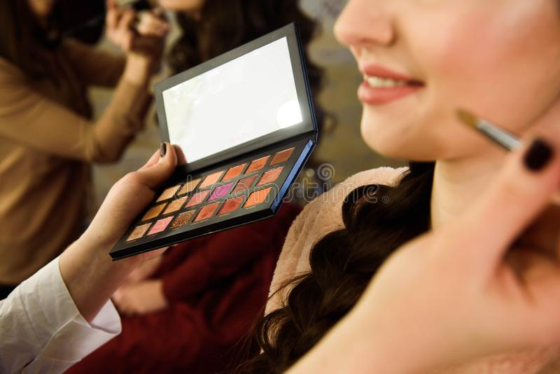 Visage concept. Close up woman getting make up on eyelids. Applying eyeshadow with brush by professional artist. stock photography