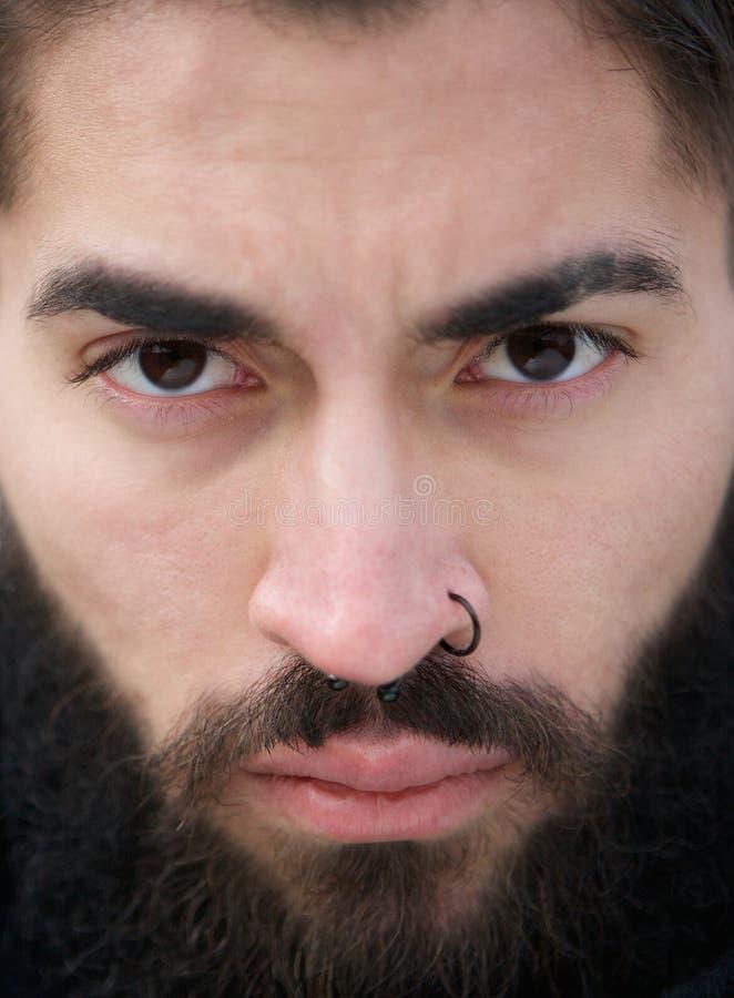 Visage d'homme avec la perforation de barbe et de nez images stock