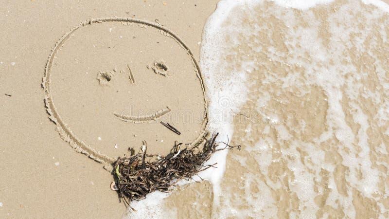 Visage d'un homme drôle peint sur le sable avec une barbe image stock