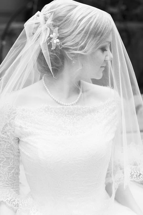 Visage d'un voile caché belle par jeune mariée image stock