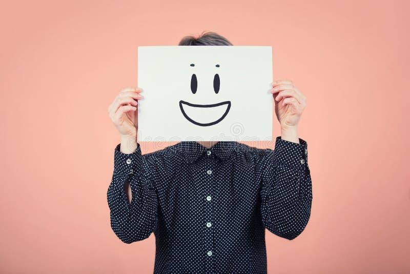 Visage de bâche de femme d'affaires utilisant une feuille de livre blanc avec le croquis d'émoticône de sourire, comme le faux ma images stock