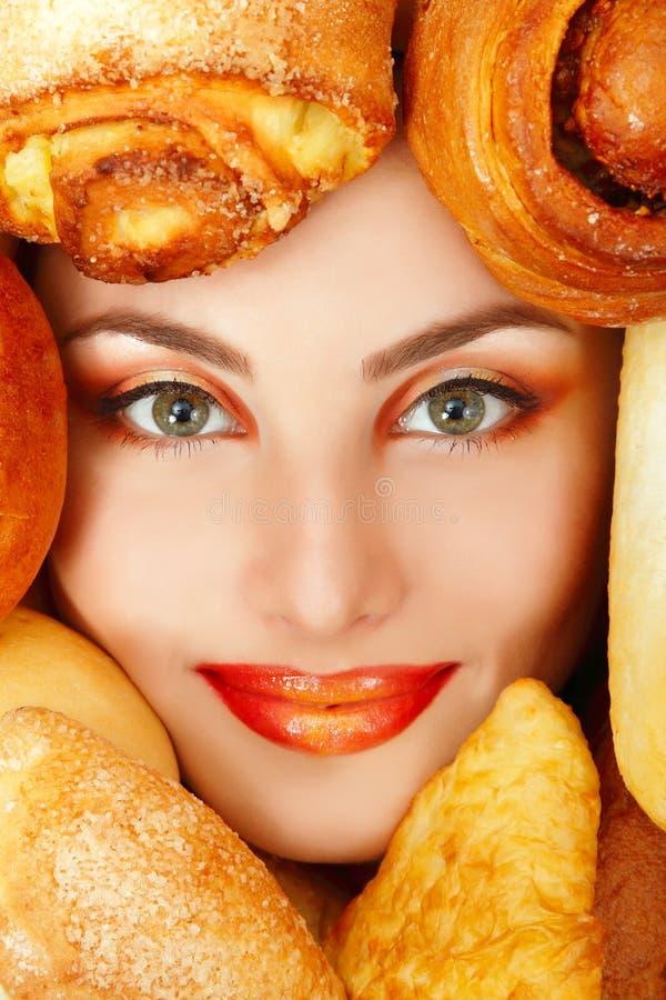 Visage de beauté de femme avec la nourriture de cuisson de petit pâté de petit pain de pain photographie stock