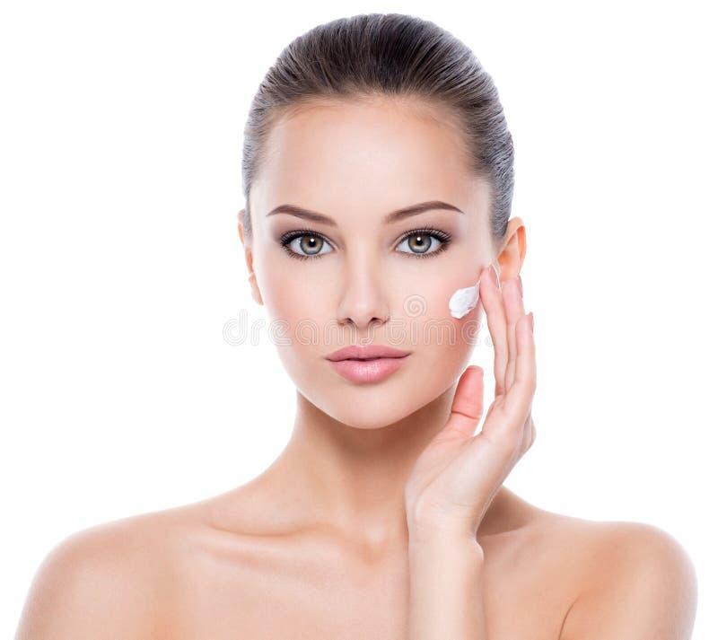Visage de beauté de la femme avec crème cosmétique sur le visage photos stock