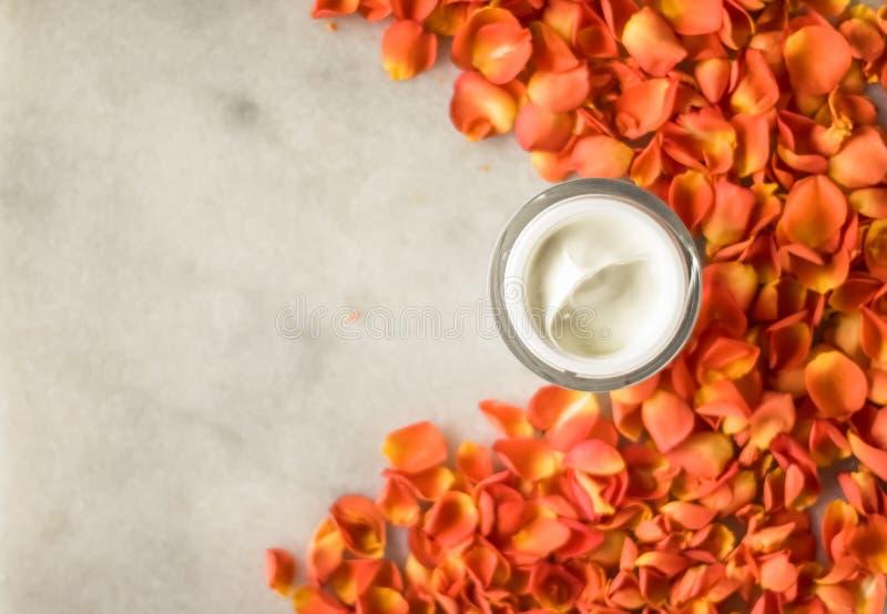 Visage de beaut? hydratant des p?tales de cr?me et de fleur sur le produit cosm?tique de marbre et de luxe images stock