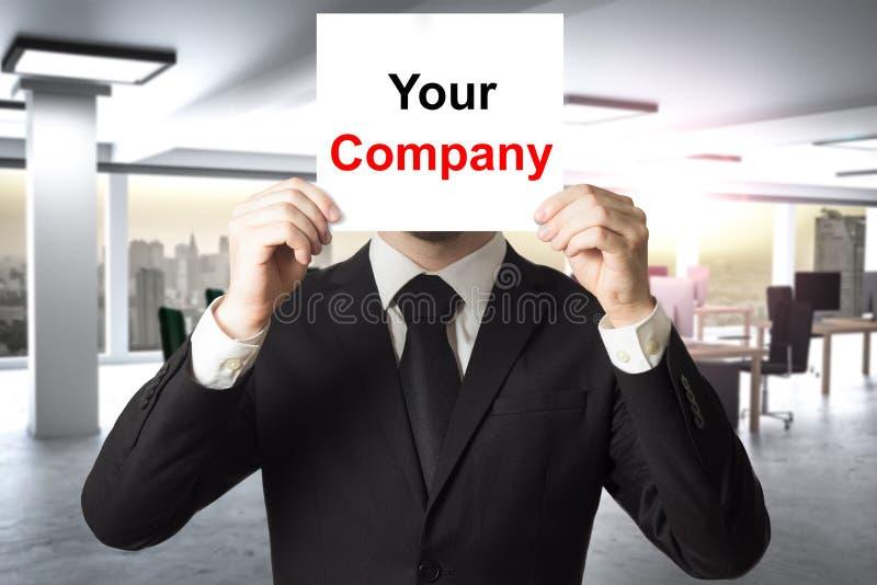 Visage de dissimulation d'homme d'affaires derrière le signe votre société photo stock