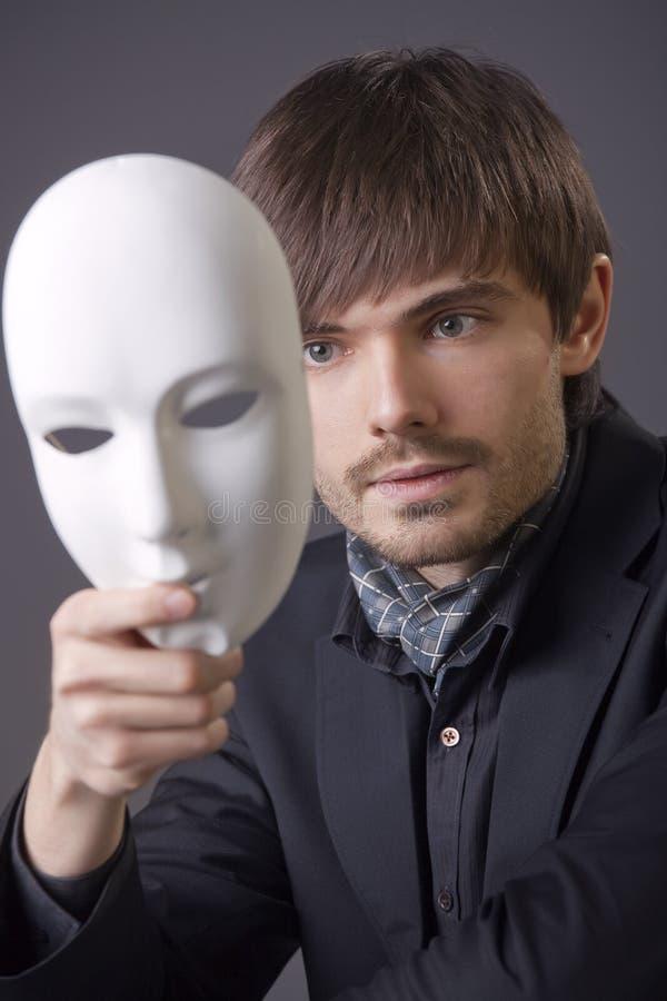 Visage de dissimulation d'homme sous le masque blanc image libre de droits