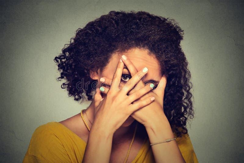 Visage de dissimulation de femme timide timide Femme jetant un coup d'oeil cependant des mains Fond gris photo stock