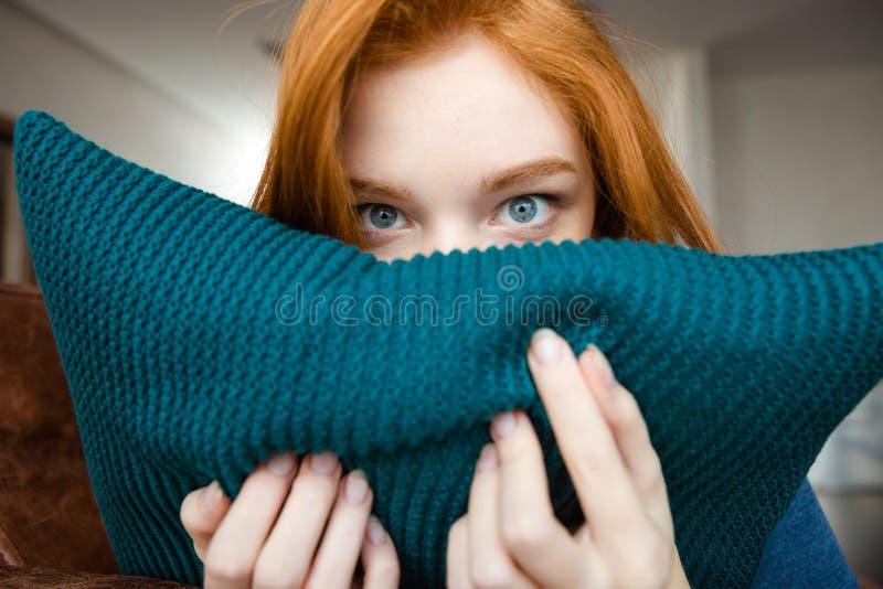 Visage de dissimulation de jolie jeune femme timide derrière l'oreiller tricoté photographie stock libre de droits
