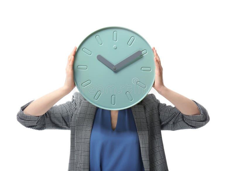 Visage de dissimulation de femme derrière l'horloge sur le fond blanc Concept de gestion du temps image stock
