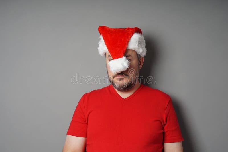 Visage de dissimulation de haineux de Noël derrière le chapeau de Santa photos libres de droits