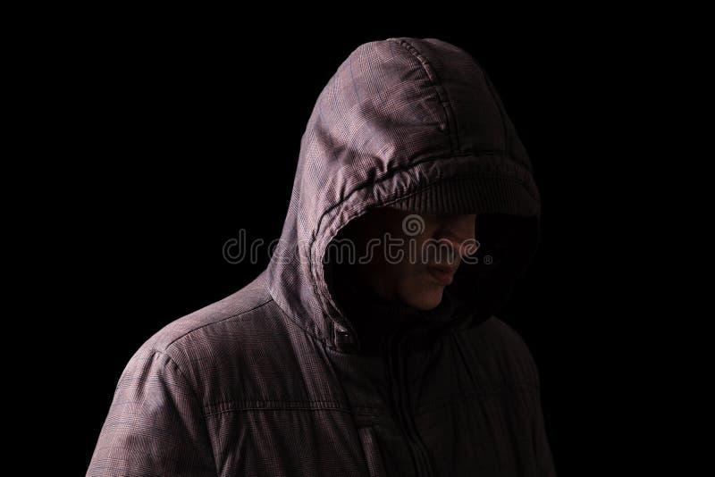 Visage de dissimulation isolé, déprimé et fragile d'homme caucasien ou blanc, se tenant dans l'obscurité photographie stock