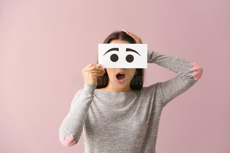 Visage de dissimulation de jeune femme émotive derrière la feuille de papier avec les yeux tirés sur le fond de couleur images stock
