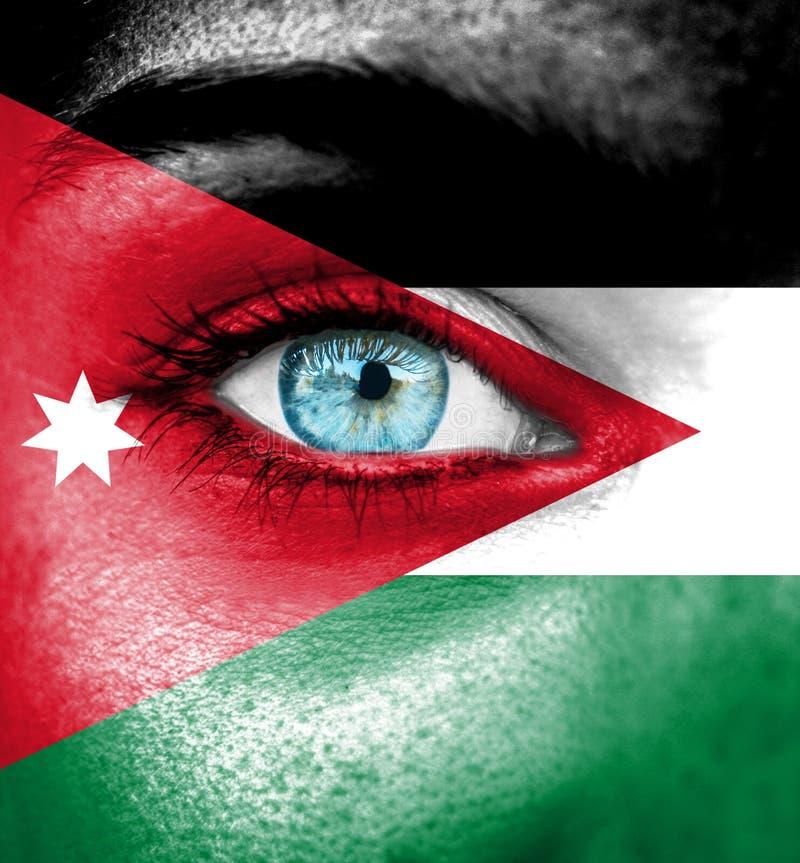 Visage de femme peint avec le drapeau de la Jordanie photographie stock libre de droits