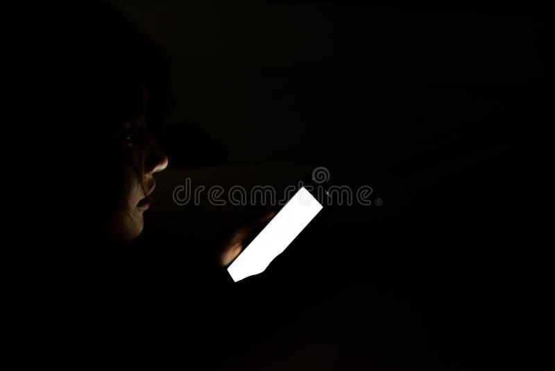 Visage de femme utilisant le téléphone intelligent sur le lit la nuit Beau gi asiatique image libre de droits