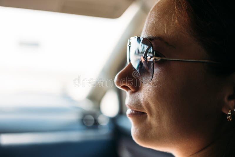 Visage de fille en verres de soleil à l'intérieur de voiture images stock