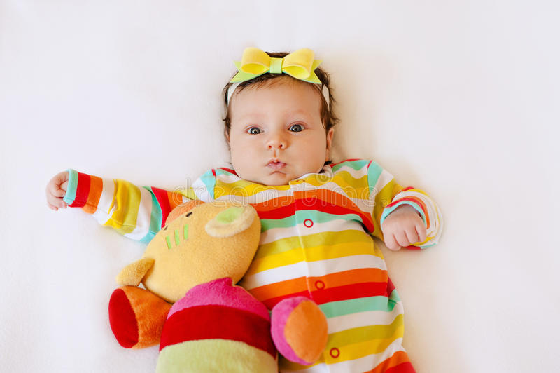 Visage de fille infantile étonnée mignonne de bébé dans des pyjamas colorés avec un arc sur sa tête, faisant l'expression drôle d photographie stock
