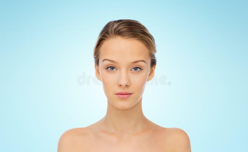 Visage de jeune femme avec les épaules nues au-dessus du bleu photos libres de droits