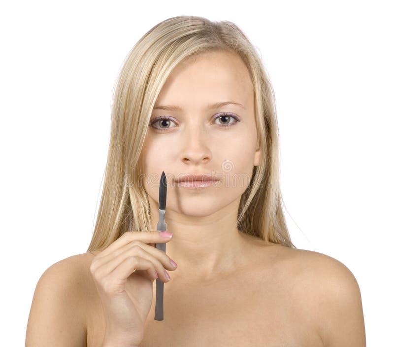 Visage de jeune femme blonde + de scalpel dans sa main images stock