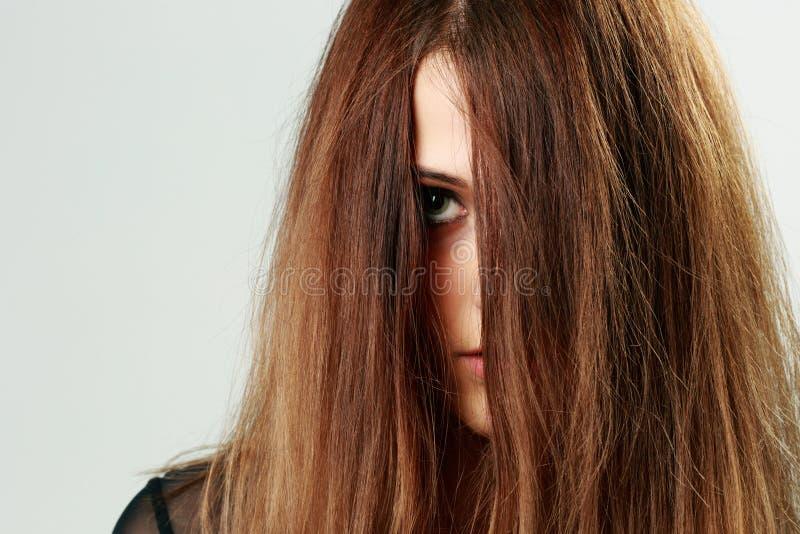 Visage de jeune femme couvert de cheveux photographie stock