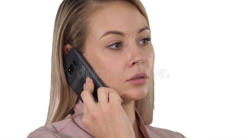 Visage de la jeune femme d'affaires gaie parlant au téléphone portable sur le fond blanc photo libre de droits