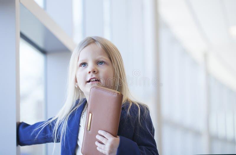 Visage de la petite fille de sourire utilisant la veste bleue tenant le portefeuille image stock