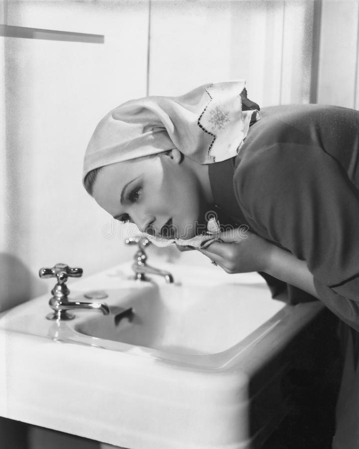 Visage de lavage de femme au-dessus d'évier photo stock