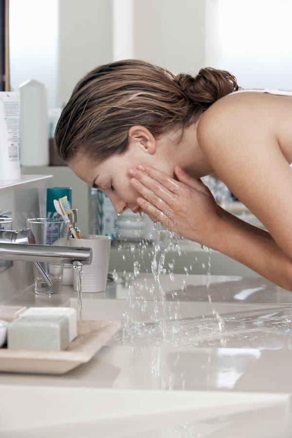 Visage de lavage de femme dans la salle de bains images stock