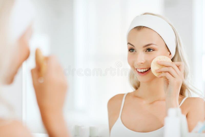Visage de lavage de jeune femme avec l'éponge à la salle de bains photos stock