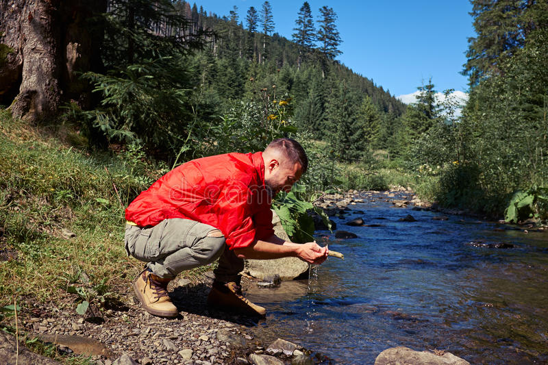 Visage de lavage de randonneur barbu positif en rivière de montagne images libres de droits