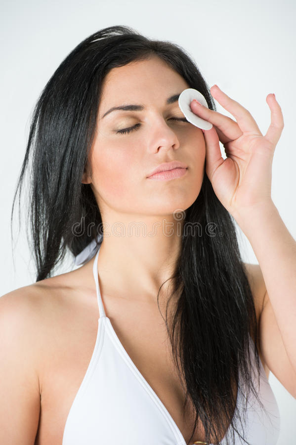 Visage de nettoyage de femme avec le tampon de coton photographie stock