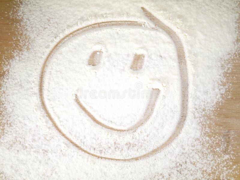 Visage de sourire sur la farine arrosée image libre de droits