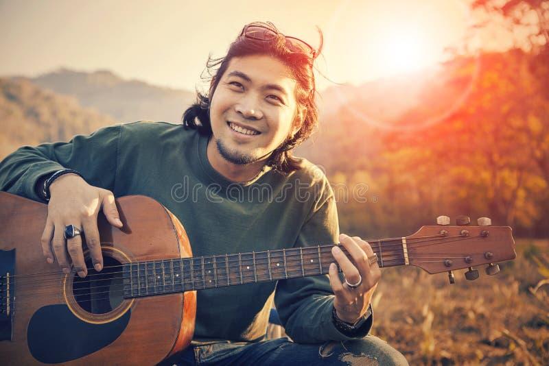 Visage de sourire toothy d'homme asiatique avec bonheur jouant la guitare et image libre de droits