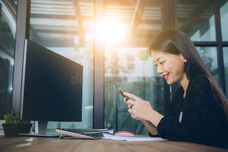 Visage de sourire Toothy de message asiatique de lecture de plus jeune femme sur l'écran intelligent de téléphone photo stock