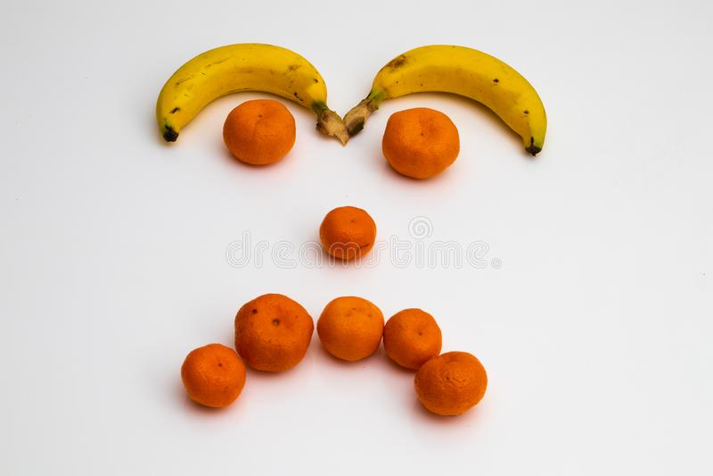 Visage des fruits sur le fond blanc visage fait avec des fruits frais banane, mandarine de mandarine photo libre de droits