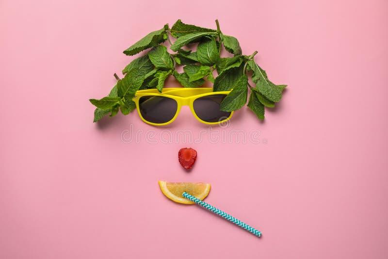 Visage drôle fait en lunettes de soleil, menthe, fraise, paille de cocktail et tranche d'agrume sur le fond de couleur image libre de droits