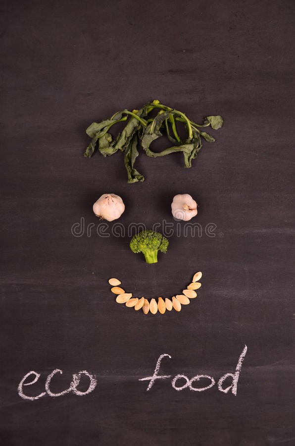 Visage drôle des légumes sur la terre noire photographie stock libre de droits