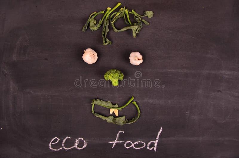 Visage drôle des légumes sur la terre noire photographie stock