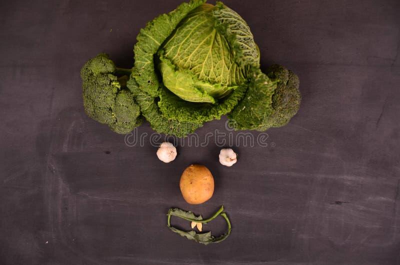 Visage drôle des légumes sur la terre noire images stock