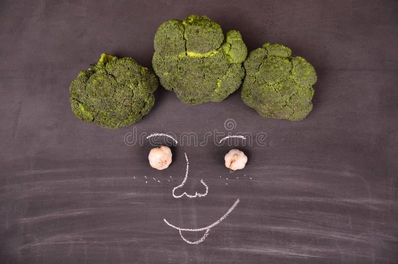 Visage drôle des légumes sur la terre noire photo libre de droits